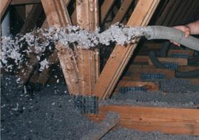 Applegate Loose-Fill Cellulose Insulation being blown in an attic.