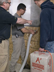 Learning how to dense-pack a wall with Applegate cellulose insulation in an Applegate training session